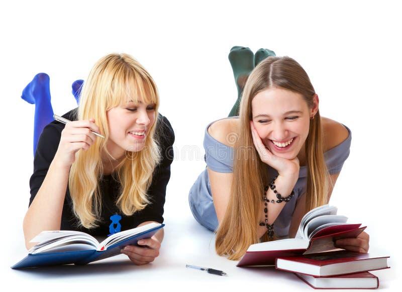 Mädchen, die auf das Fußboden- und Lesebuch legen lizenzfreie stockfotografie