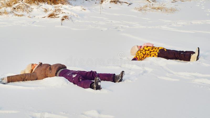 Mädchen, die auf den Schnee legen lizenzfreie stockfotografie