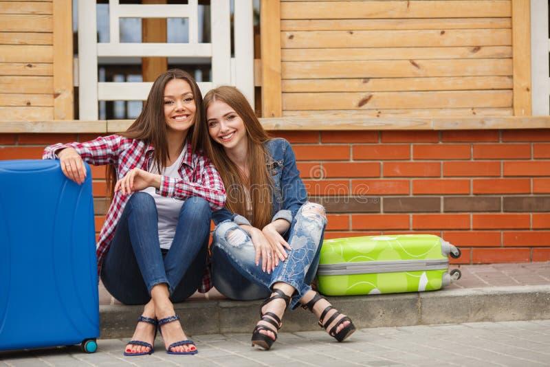 Mädchen, die auf den Zug sitzt auf dem Koffer warten lizenzfreie stockfotografie