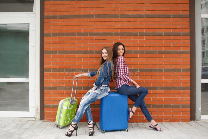 Mädchen, die auf den Zug sitzt auf dem Koffer warten stockbilder