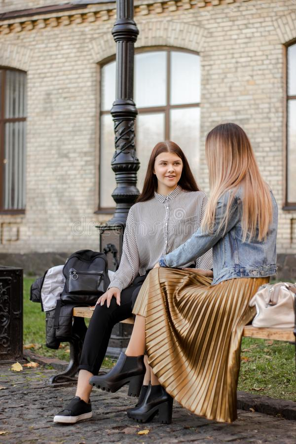 Mädchen, die auf einer Bank im Herbstpark sprechen lizenzfreie stockfotos
