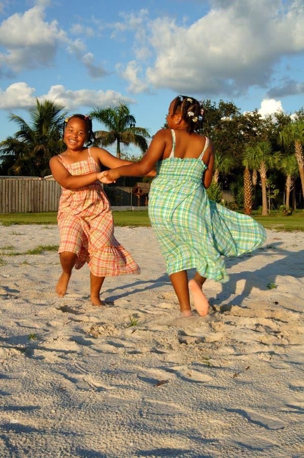 Mädchen, die auf Sand am Strand tanzen lizenzfreies stockbild
