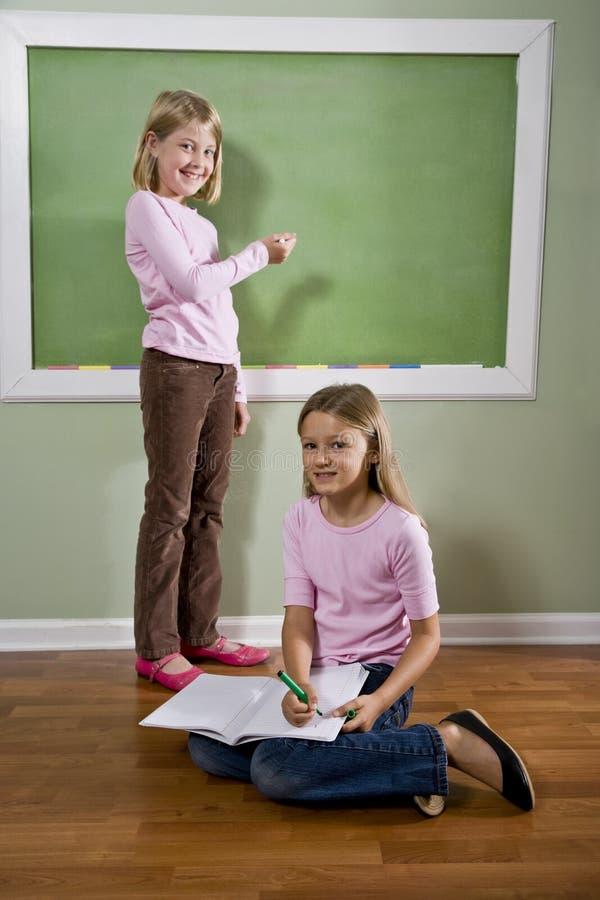 Mädchen, die auf Tafel schreiben und Heimarbeit tun stockbild