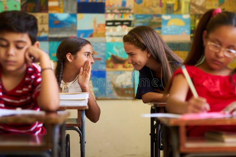 Mädchen, die in der Schule während des Aufnahme-Tests in der Klasse betrügen lizenzfreie stockfotos