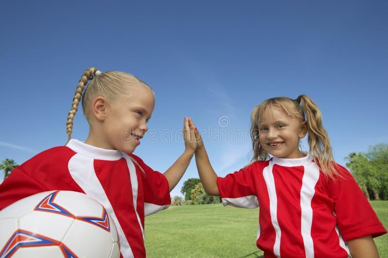 Mädchen, die ein hoch--Fünf auf Fußballplatz geben stockfotografie