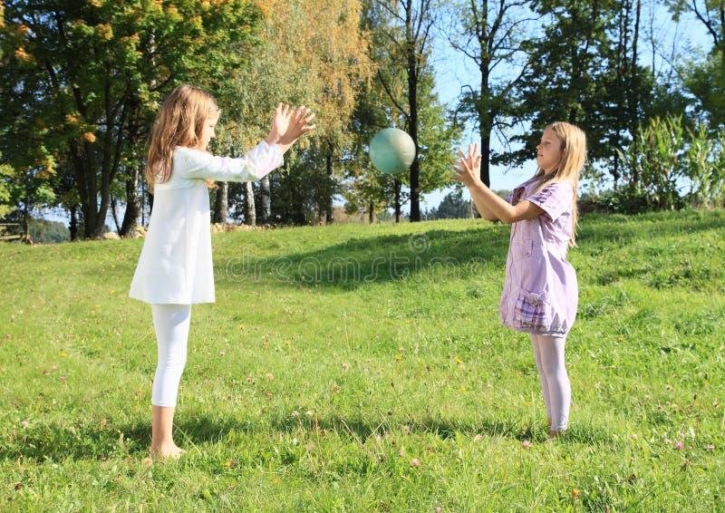 Mädchen, die einen Ball werfen stockfotos