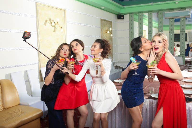 Mädchen, die Gläser Cocktails an der Partei klirren stockfotografie