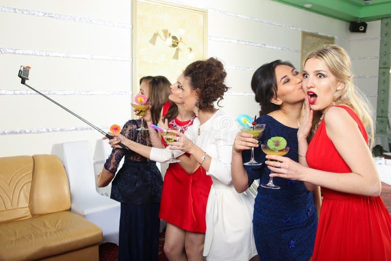 Mädchen, die Gläser Cocktails an der Partei klirren lizenzfreie stockbilder