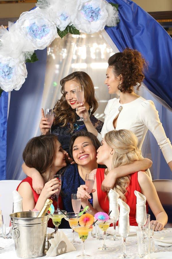 Mädchen, die Gläser Cocktails an der Partei klirren stockbilder