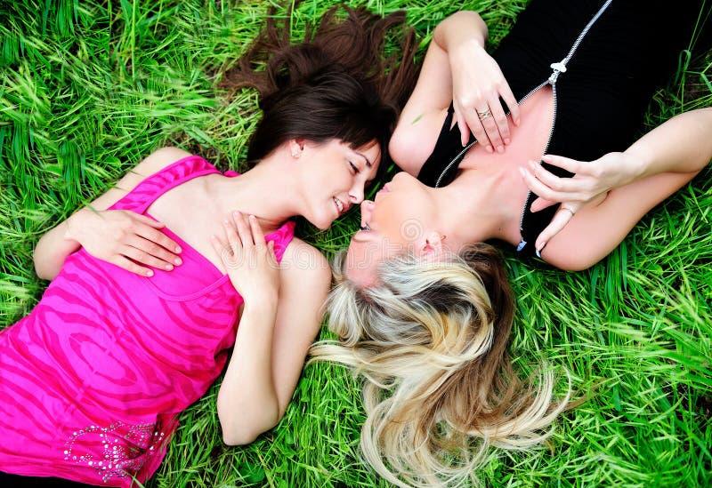 Mädchen, die in Gras legen stockfotografie