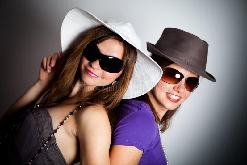 Mädchen, die Hüte und Gläser tragen stockbilder