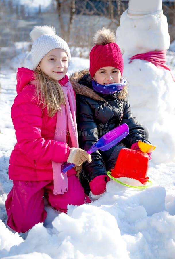 Mädchen, die im Winter mit Schaufeln spielen stockbilder