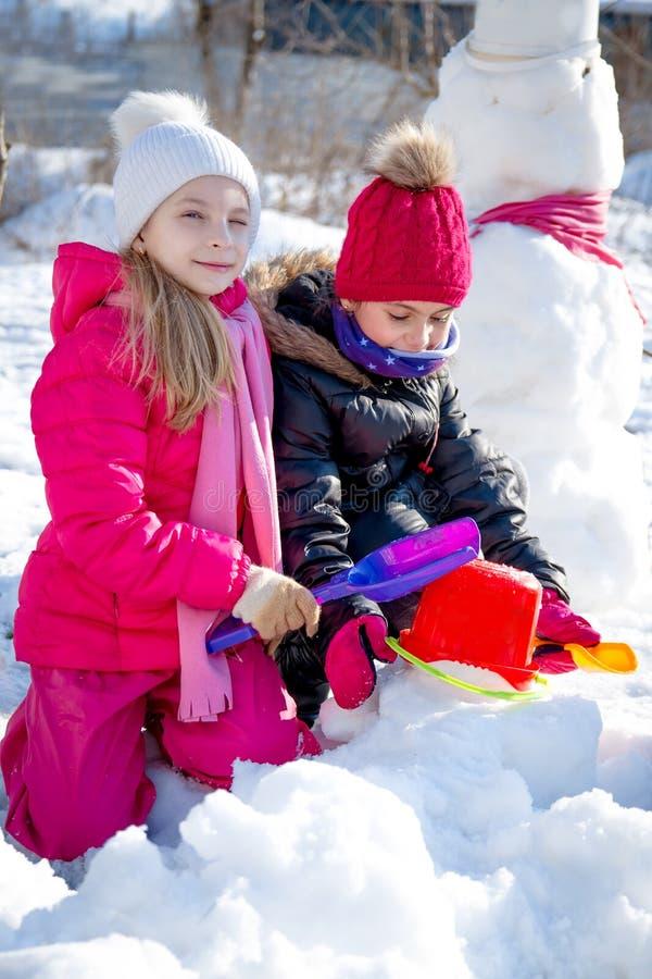 Mädchen, die im Winter mit Schaufeln spielen stockbild