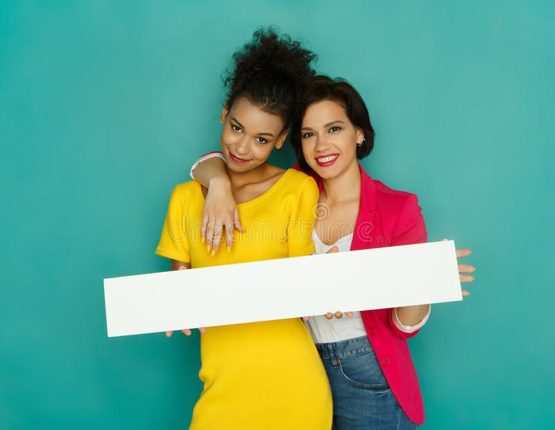 Mädchen, die leeres weißes Brett am azur Studiohintergrund halten stockfotografie