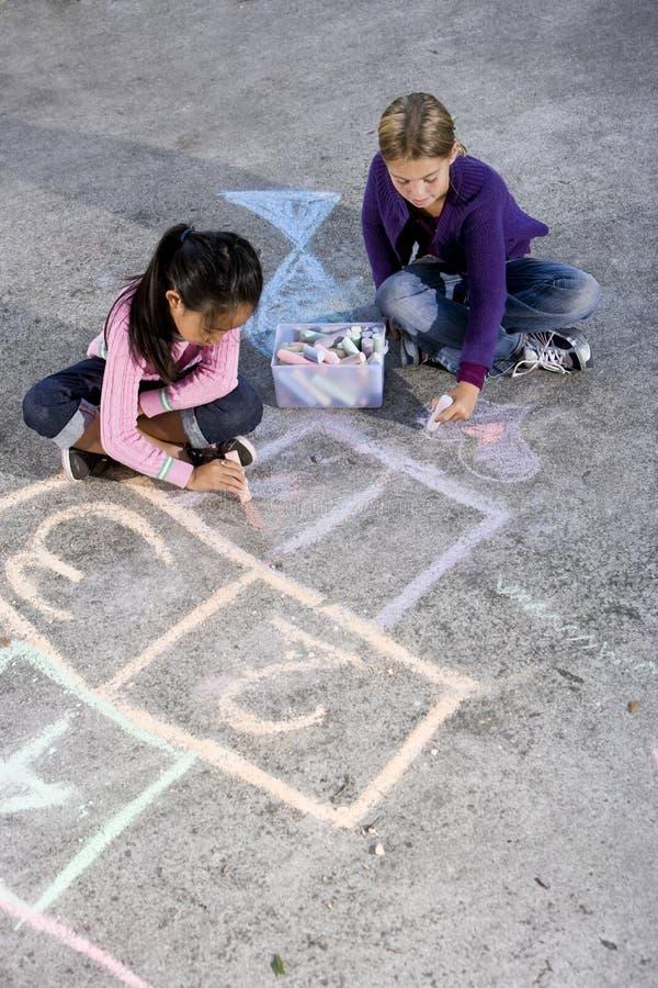 Mädchen, die mit Bürgersteigkreide spielen lizenzfreies stockbild
