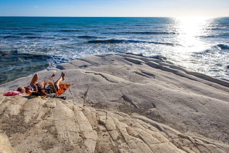 Mädchen, die mit Buch und erhalten auf, den felsigen weißen Klippen ein Sonnenbad zu nehmen sich entspannen lizenzfreie stockfotos