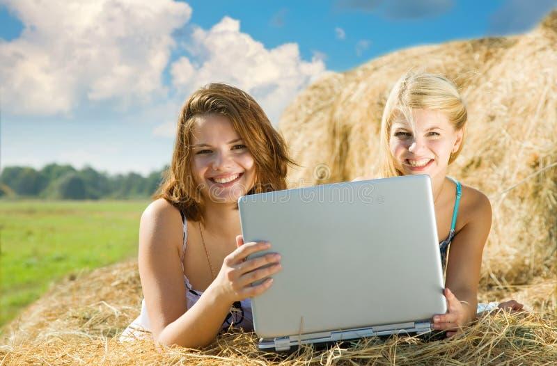 Mädchen, die mit Laptop sich entspannen stockfoto