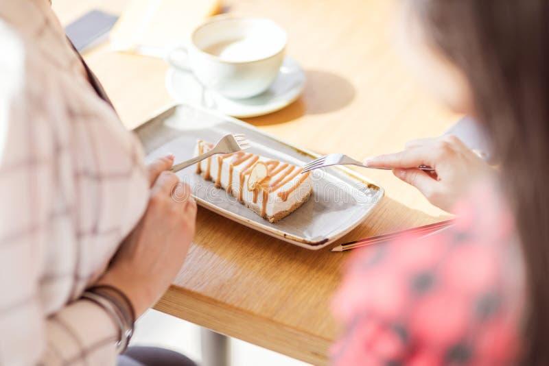 Mädchen, die Süßspeise mit Gabeln am Café, Kaffeepause essen lizenzfreies stockbild