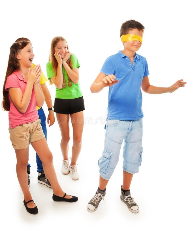 Mädchen, die vom Jungen mit versteckten Augen sich verstecken stockbild