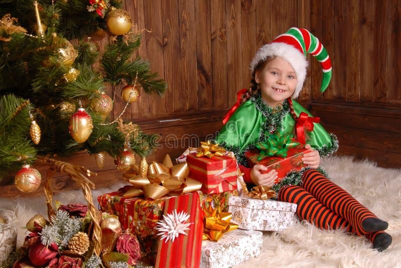Mädchen - die Weihnachtselfe mit einem Geschenk stockfoto