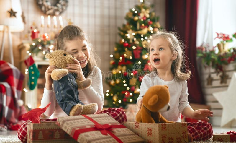 Mädchen, die Weihnachtsgeschenke öffnen lizenzfreie stockfotos