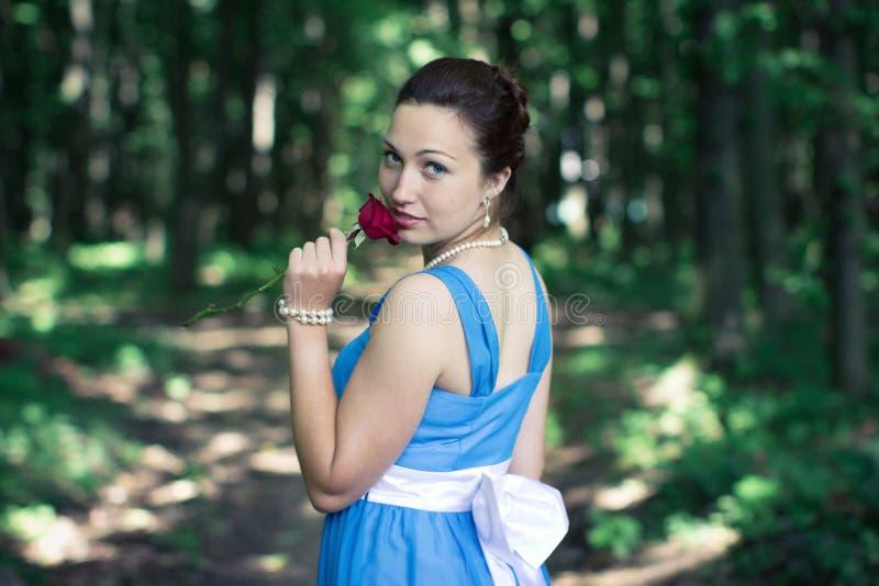 Mädchen dreht sich herum mit Rotrose in ihrer Hand im dunklen Wald lizenzfreie stockfotos