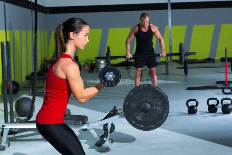 Mädchen Dumbbell und Manngewichtsanhebenstangen-Training stockfotografie