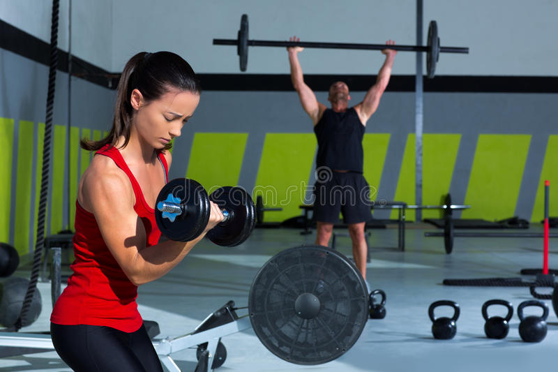 Mädchen Dumbbell und Manngewichtsanhebenstangen-Training lizenzfreie stockfotos