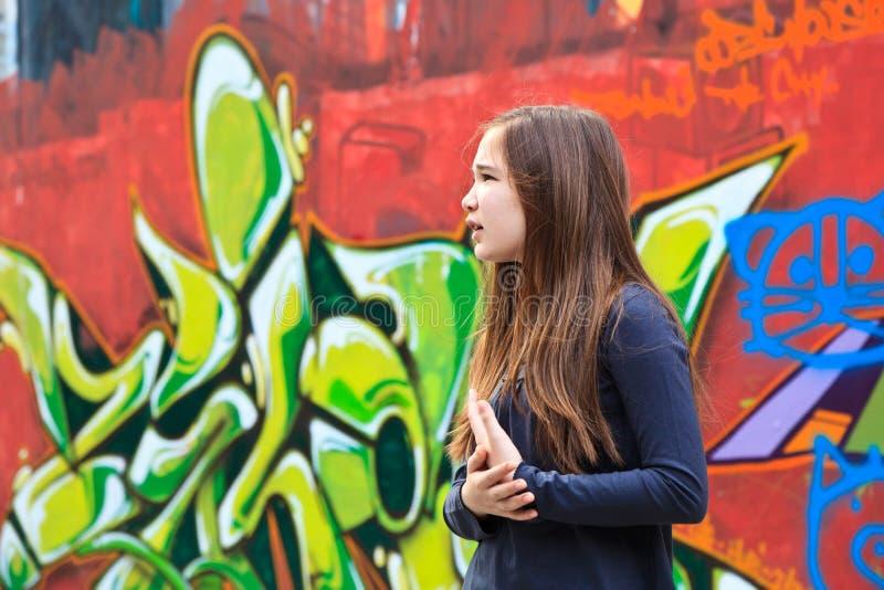 Mädchen durch eine Graffitiwand lizenzfreies stockfoto