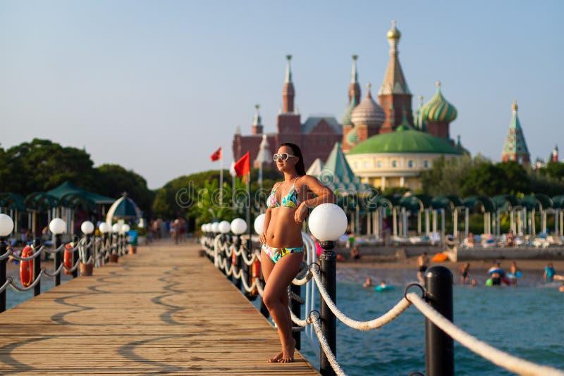 Mädchen in einem Badeanzug auf dem Pier auf dem Hintergrund des Hotels Mädchen, das auf dem hölzernen Pier auf dem Strand, gegen  stockbild