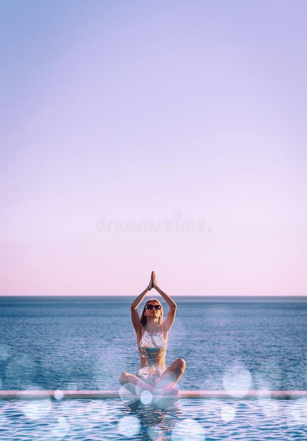 Mädchen in einem Badeanzug nahe dem panoramischen Pool auf dem Hintergrund des Meeres entspannt sich stockfotos