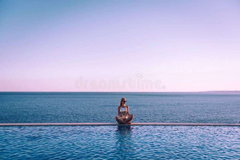 Mädchen in einem Badeanzug nahe dem panoramischen Pool auf dem Hintergrund des Meeres entspannt sich lizenzfreie stockbilder