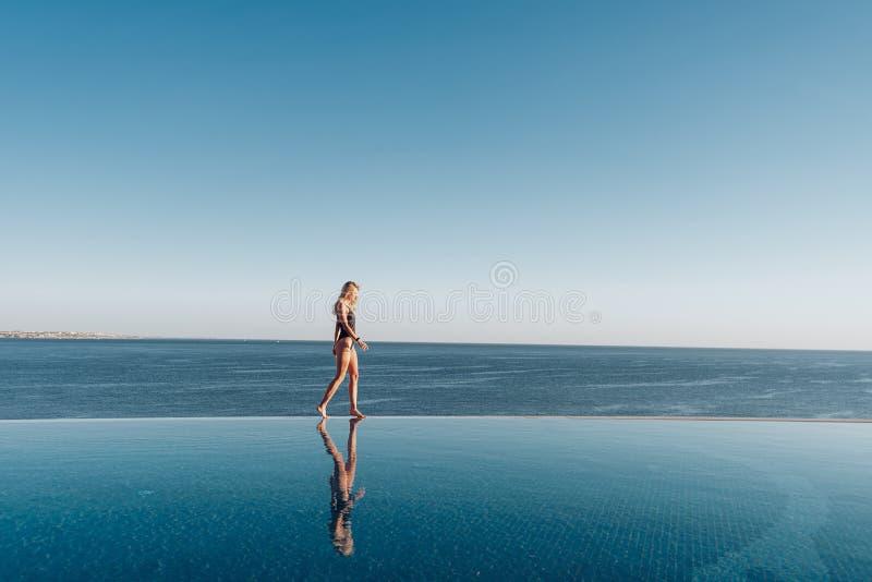 Mädchen in einem Badeanzug nahe dem panoramischen Pool auf dem Hintergrund des Meeres entspannt sich lizenzfreies stockfoto