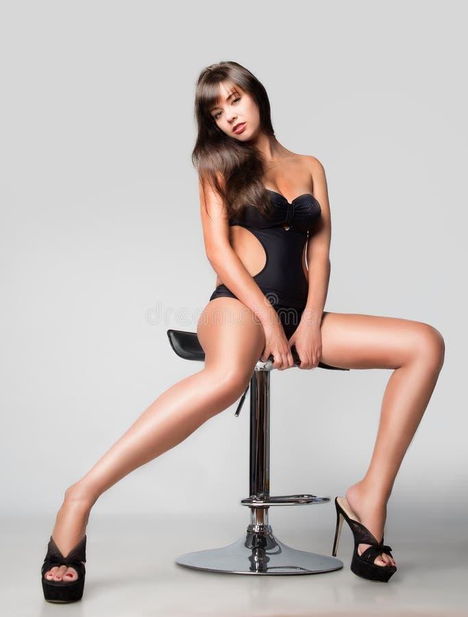 Mädchen in einem Badeanzug. Sitzen auf einem Stuhl. stockbilder