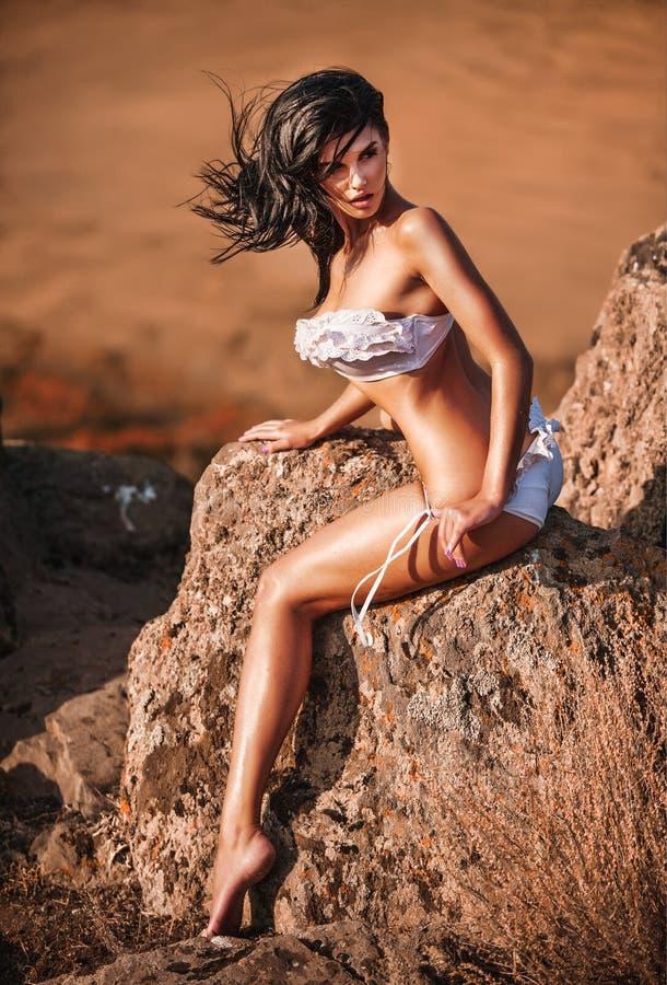 Mädchen in einem Badeanzug sitzt auf einem Felsen lizenzfreies stockfoto