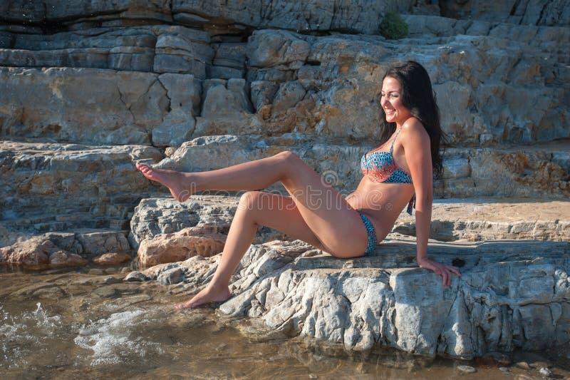 Mädchen in einem Badeanzug, Spritzwasser mit ihrem Fuß Ein schöner Brunette genießt ein warmes Meer-vada stockfoto