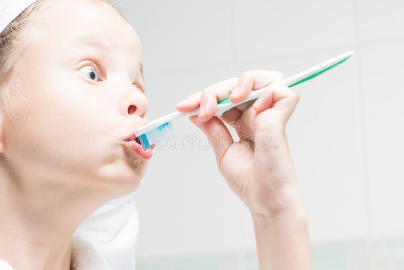 Mädchen in einem Badenraum, der herum mit einer Zahnbürste macht ein erstaunliches Gesicht täuscht stockbilder