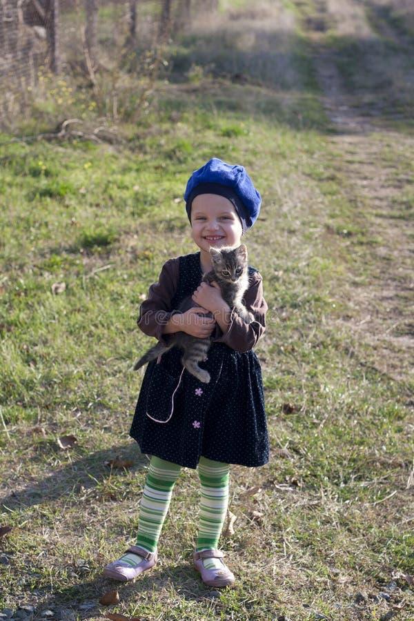 Mädchen in einem Barett lächelt mit einem Kätzchen auf seinen Händen stockfotos