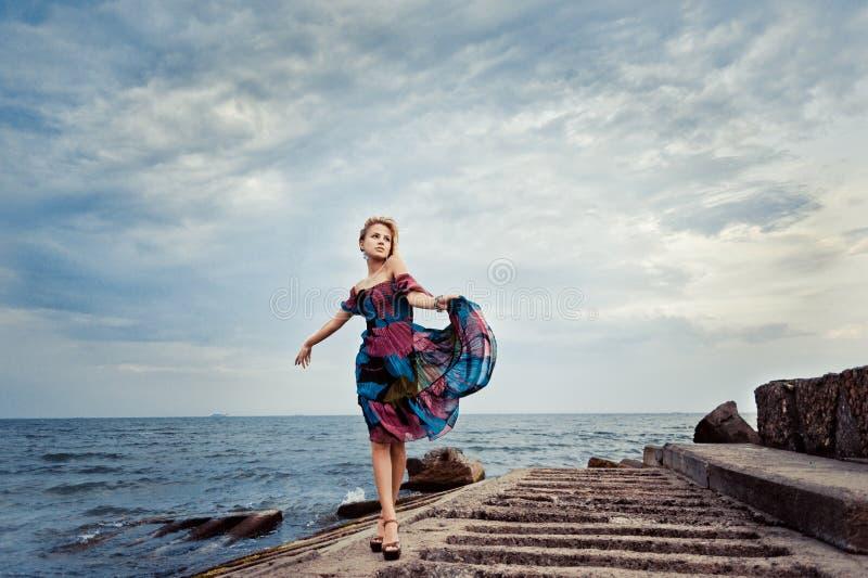 Mädchen in einem bunten Kleid auf dem Pier stockfoto