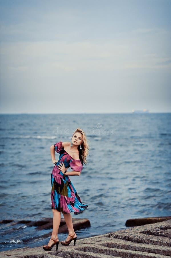 Mädchen in einem bunten Kleid auf dem Pier stockbilder