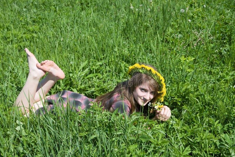 Mädchen in einem Chaplet, der von der Wiese liegt stockfotos