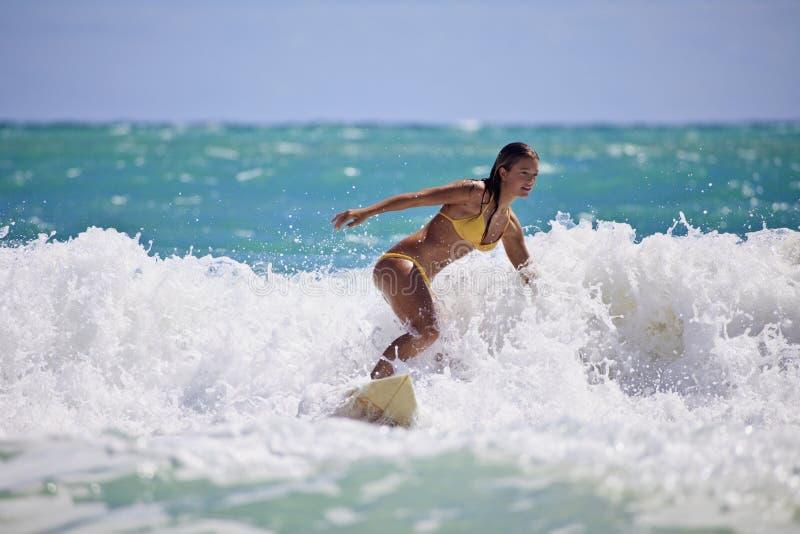 Mädchen in einem gelben surfenden Bikini stockfotos