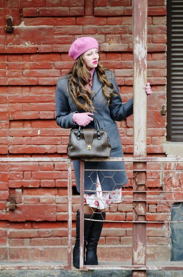 Mädchen in einem grauen Mantel und in einem rosa Barett in der Straße der alten Stadt lizenzfreie stockfotos