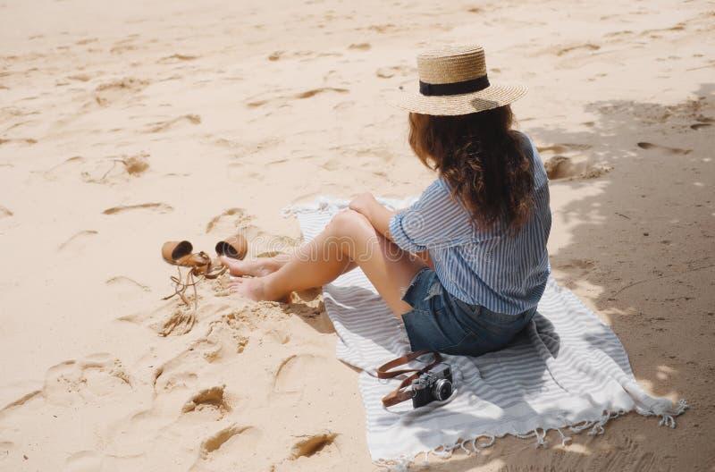 Mädchen in einem Hut auf dem Strand sitzt auf dem Sand unter einem Baum stockbilder