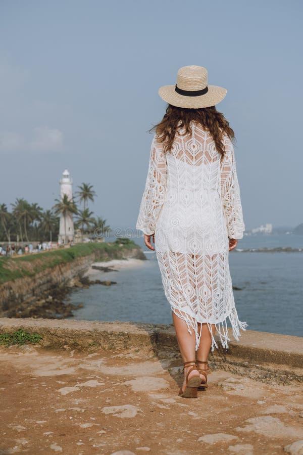 Mädchen in einem Hut, der den Ozean betrachtet lizenzfreies stockfoto