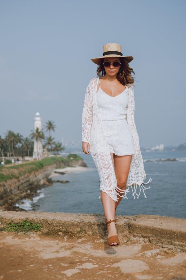 Mädchen in einem Hut, der in die weiße Kleidung des Windlichtes gehend um den Ozean wellenartig bewegt stockbild