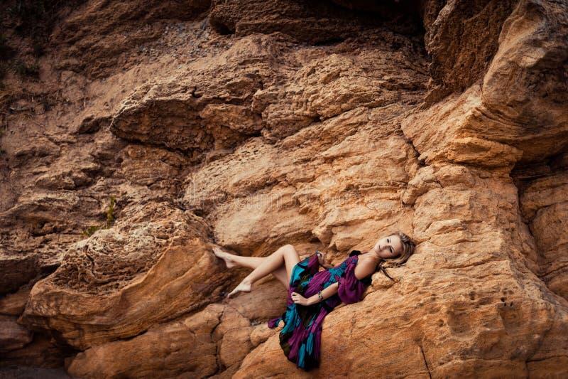 Mädchen in einem Kleid auf einem Felsen lizenzfreie stockfotos