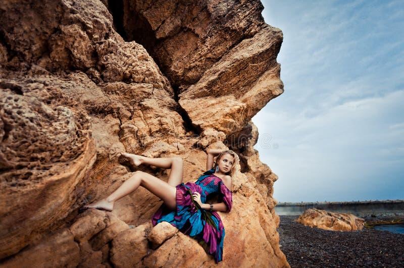 Mädchen in einem Kleid auf einem Felsen lizenzfreie stockfotografie