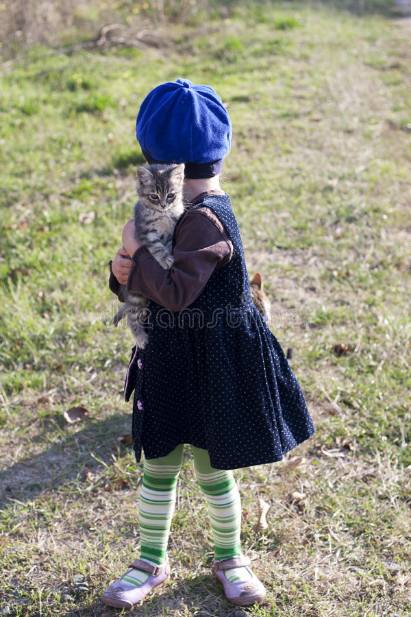 Mädchen in einem Kleid und nehmen ein kleines Kätzchen an Hand lizenzfreie stockfotos