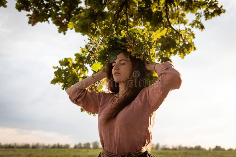 Mädchen in einem Kranz von Eichenblättern unter einer Eiche lizenzfreie stockfotos